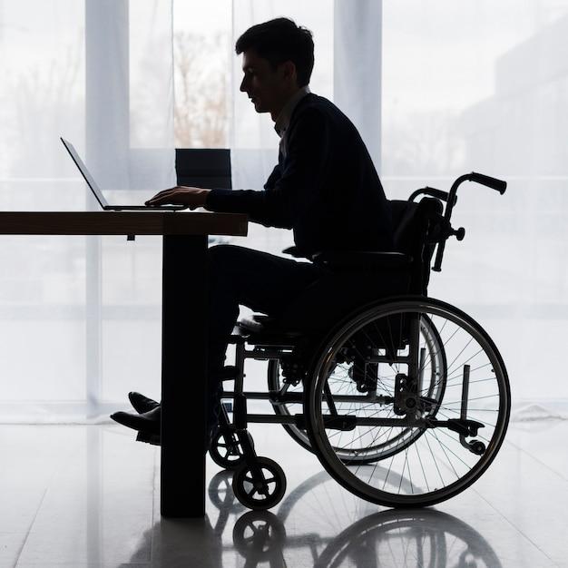 Silueta, de, um, homem negócios, sentando, ligado, cadeira rodas, usando, laptop, ligado, tabela Foto gratuita