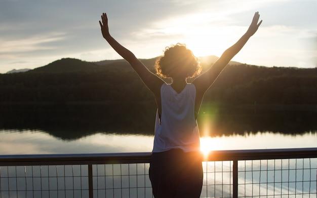 Silueta, de, um, livre, e, feliz, yowom, com, mãos cima, enjoing, porão, ligado, um, lago Foto Premium