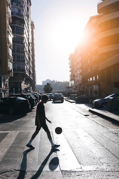 Silueta, de, um, menino adolescente, jogando basquetebol, ligado, rua, em, cidade Foto gratuita
