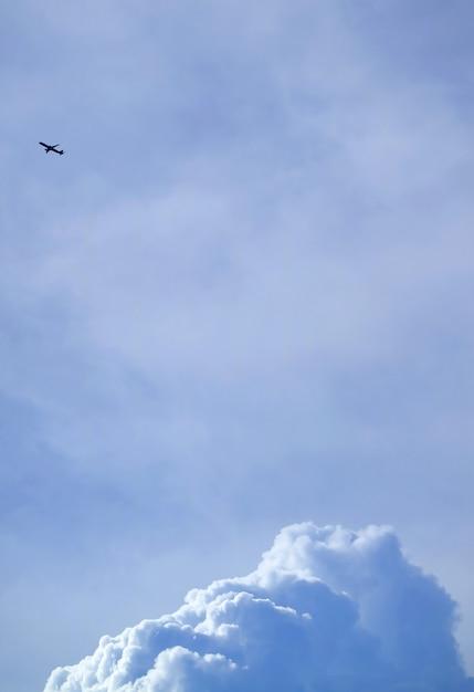 Silueta, de, um, voando, avião, ligado, luminoso azul, céu nublado, com, nuvens cumulus Foto Premium