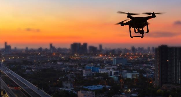 Silueta, de, zangão, voando, cidade, em, pôr do sol Foto Premium