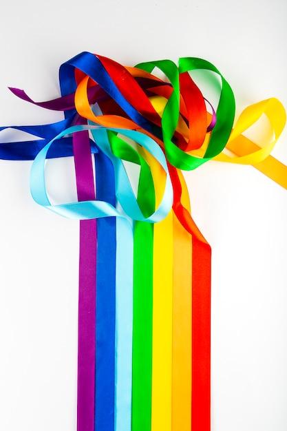 Símbolo da bandeira de lgbt feito de fitas do cetim em um fundo branco. um arco-íris de fitas se mistura entre si Foto Premium