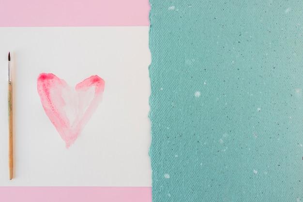 Símbolo do coração em papel branco, pincel e folha azul Foto gratuita