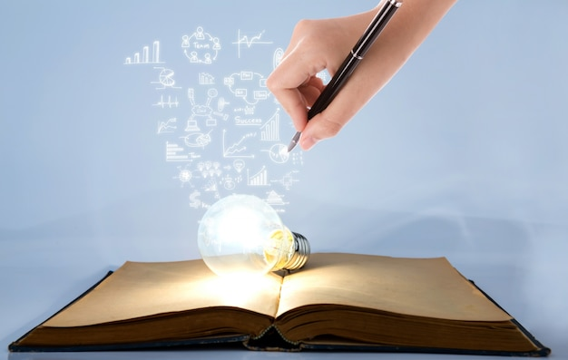 Símbolos de desenho pessoa saindo de uma lâmpada em cima de um livro Foto gratuita