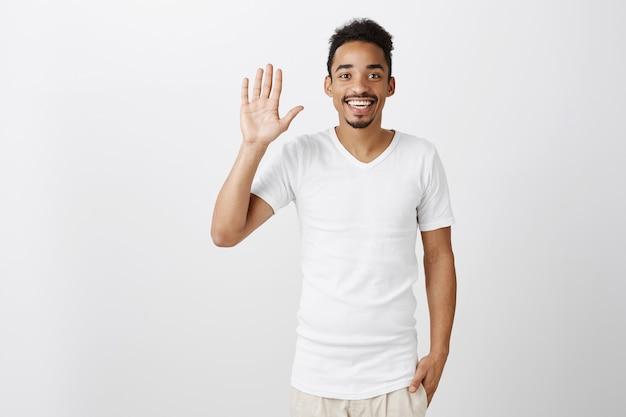 Simpático cara de pele escura acenando com a mão, dizendo olá, cumprimentando ou dando as boas-vindas a pessoa, sorrindo alegre Foto gratuita