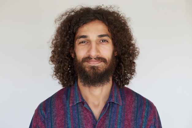 Simpático rapaz moreno encaracolado, de aspecto simpático, com uma exuberante barba sorrindo suavemente, vestindo uma camisa listrada multicolorida e de bom humor Foto gratuita