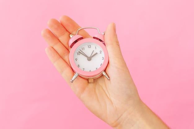 Simplesmente desenhe a mão de uma mulher feminina segurando um despertador com sino duplo isolado na mesa rosa Foto Premium