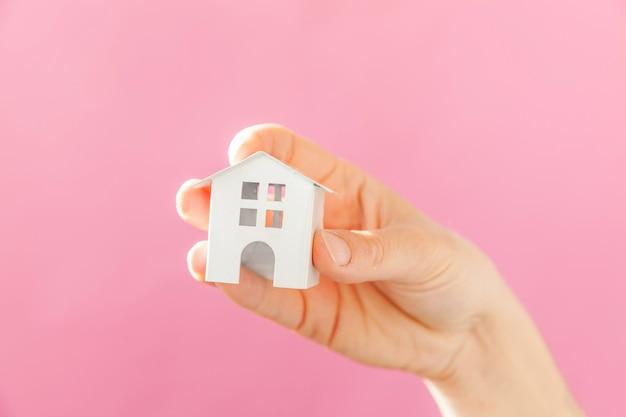 Simplesmente projete a mão de mulher feminina segurando a casa de brinquedo em miniatura branca isolada no fundo na moda colorido pastel rosa Foto Premium