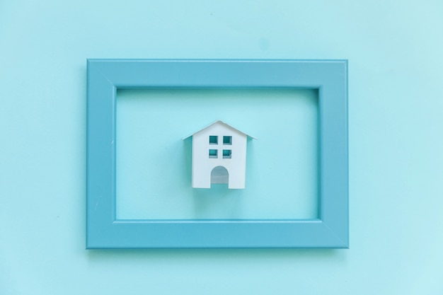 Simplesmente projete com casa de brinquedo branco em miniatura no quadro azul isolado no fundo azul colorido pastel moderno Foto Premium