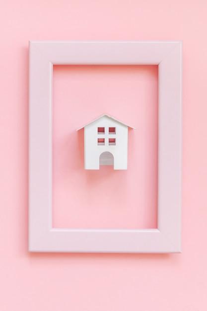 Simplesmente projete com casa de brinquedo branco em miniatura no quadro rosa isolado no fundo na moda colorido pastel rosa Foto Premium