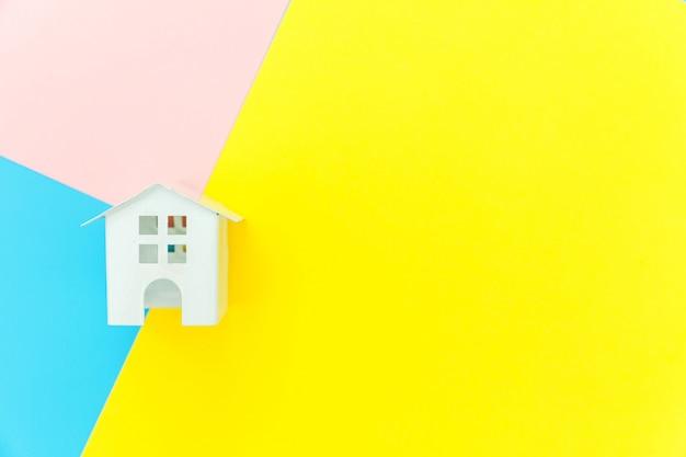 Simplesmente projete com casa de brinquedo em miniatura branca isolada no fundo rosa amarelo azul Foto Premium