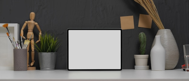 Simule o tablet em uma mesa de trabalho moderna com pincéis de pintura e decorações Foto Premium