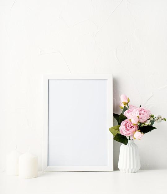 Simule uma moldura branca na parede com peônias e velas brancas Foto Premium