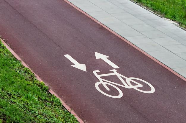 Sinais de pista de bicicleta com setas no caminho de bicicleta de cidade vermelha Foto Premium