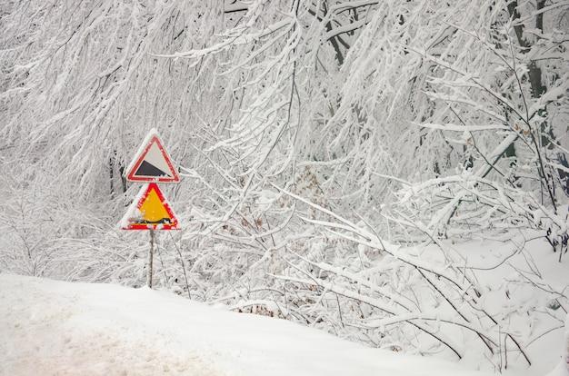 Sinais de trânsito nos galhos cobertos de neve Foto Premium