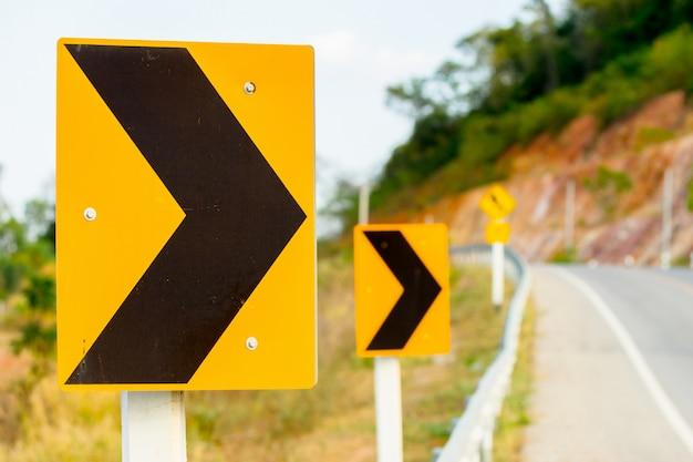 Sinal amarelo de perigo de precaução de uma estrada curvada Foto Premium