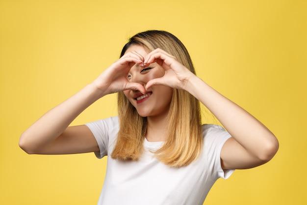 Sinal asiático novo da mão do coração da mostra da mulher isolado no fundo amarelo. Foto Premium