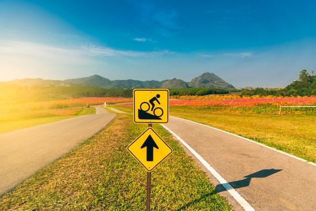 Sinal da bicicleta à estrada íngreme com fundo da cordilheira e do céu azul. Foto Premium
