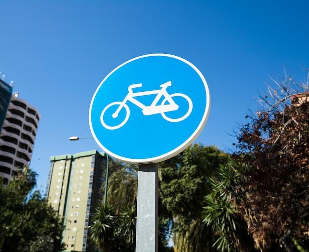 Sinal de caminho de bicicleta circular contra o céu azul Foto gratuita