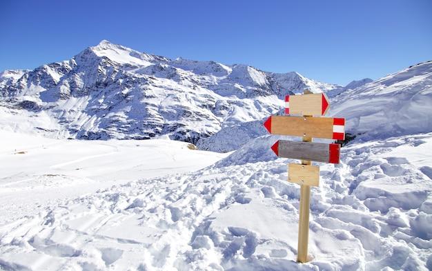 Sinal de direção na estância de esqui nos alpes italianos. panorama de montanhas de inverno com placa de madeira, indicando o caminho. conceito abstrato Foto Premium