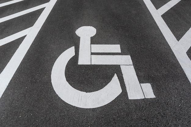 Sinal de estacionamento deficiente / incapacitado pintado no asfalto da estrada. Foto Premium
