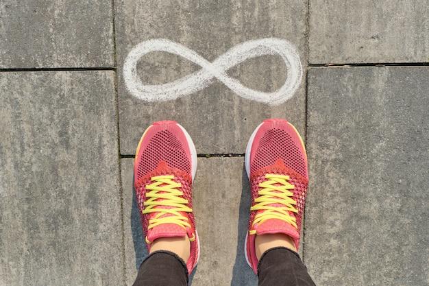 Sinal de infinito na calçada cinza com pernas de mulher no tênis Foto Premium
