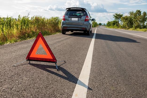 Sinal de parada de emergência e carro quebrado na estrada Foto Premium
