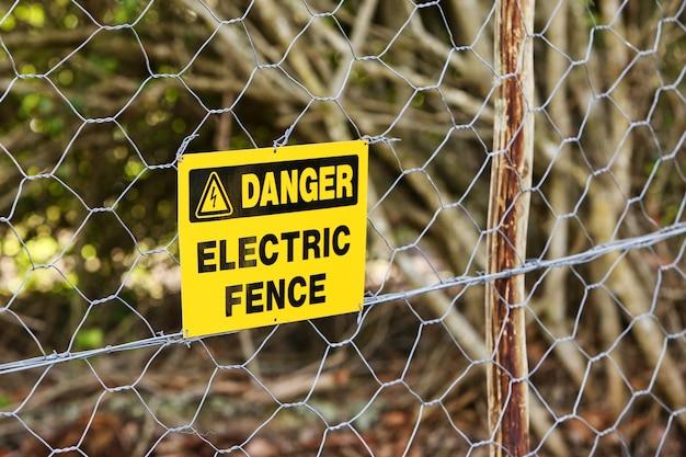Sinal de perigo pendurado na cerca elétrica Foto gratuita