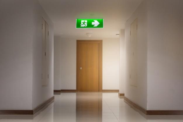 Sinal de saída de emergência verde no hotel mostrando o caminho para escapar Foto Premium