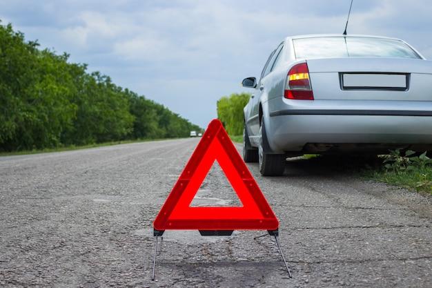 Sinal vermelho de parada de emergência e quebrado carro prateado na estrada Foto Premium