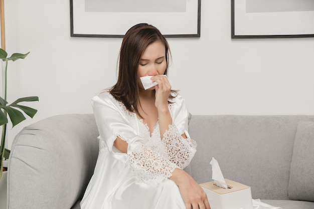 Sintomas de rinite alérgica em mulheres mulher doente, vestindo pijamas brancos, resfriada assoando o nariz em um lenço de papel em casa Foto Premium
