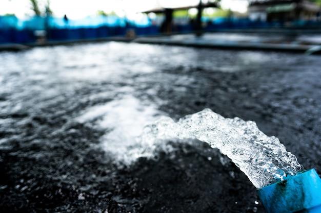 Sistema de tratamento de fluxo de água a partir do tubo da bomba de água. movimento da água que jorra fora da tubulação da piscicultura da carpa de koi pond para o oxigênio. Foto Premium