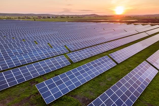Sistema solar azul dos painéis voltaicos da foto produzindo a energia limpa renovável na paisagem rural e no fundo do sol de ajuste. Foto Premium