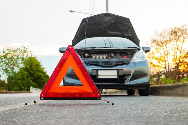Situação inesperada, sinal de parada de emergência e carro da cidade quebrado na estrada. Foto Premium