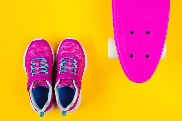 Skate rosa e tênis em fundo amarelo plano leigos Foto Premium
