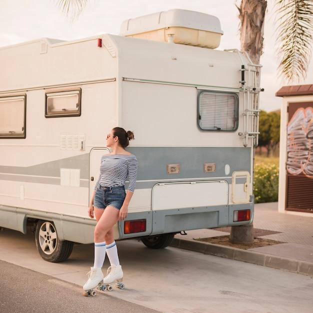 Skatista feminina inclinando-se perto de caravana a desviar o olhar Foto gratuita