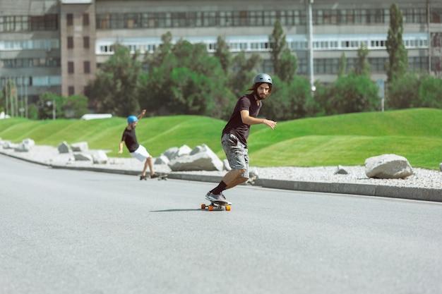 Skatistas fazendo uma manobra na rua da cidade em dia ensolarado Foto gratuita