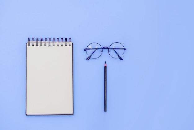 Sketchbook espiral simulado até óculos e lápis preto. Foto Premium