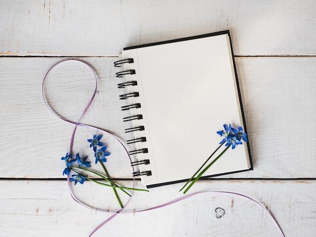 Sketchbook, página em branco, flor brilhante e fita rosa Foto Premium