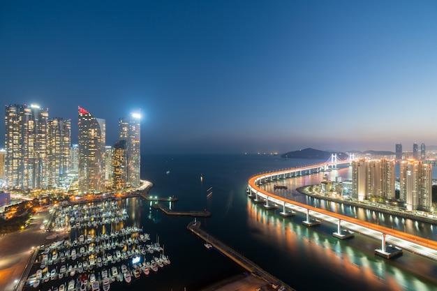 Skyline da cidade de busan na opinião da skyline da área do distrito financeiro de haeundae da parte superior do telhado na noite em busan, coreia do sul. turismo asiático, vida moderna na cidade ou conceito de finanças e economia empresarial Foto Premium