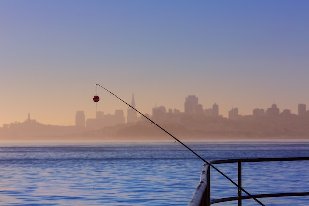 Skyline de nevoeiro de são francisco com vara de pescar na névoa califórnia Foto Premium