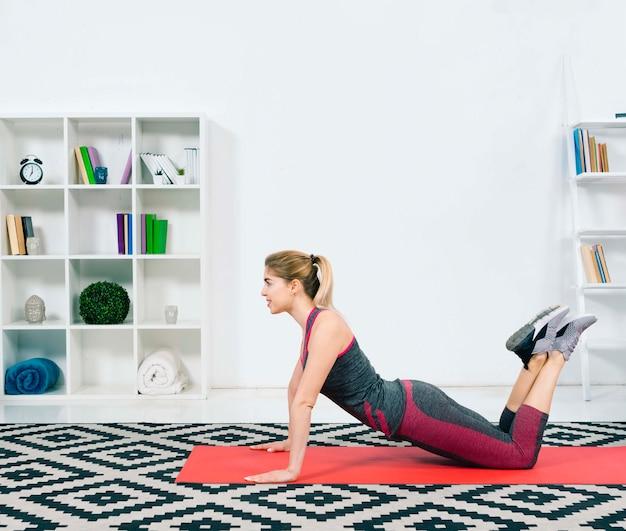 Slim fit jovem fazendo exercício no tapete de exercícios vermelho Foto gratuita