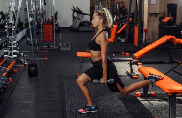 Slim fit mulher no sportswear praticando lunges com halteres nas mãos no ginásio. conceito de treinamento com pesos livres. treino funcional Foto Premium