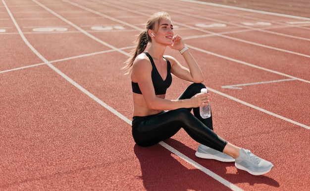 Slim fit mulher no sportwear ouvindo música com fones de ouvido enquanto está sentado em uma pista do estádio com um revestimento vermelho ao ar livre. corrida, Foto Premium