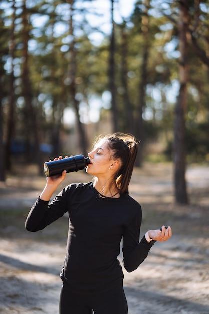Slim jovem mulher água potável após o treino Foto gratuita