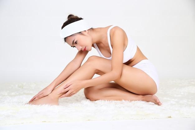 Slim mulher jovem e bonita está tratando seus pés Foto gratuita