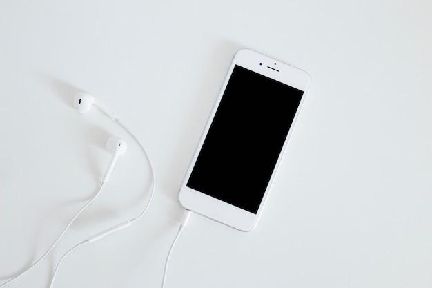Smartphone com fone de ouvido isolado no fundo branco Foto gratuita