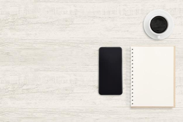 Smartphone com notebook e uma xícara de café na madeira. Foto Premium