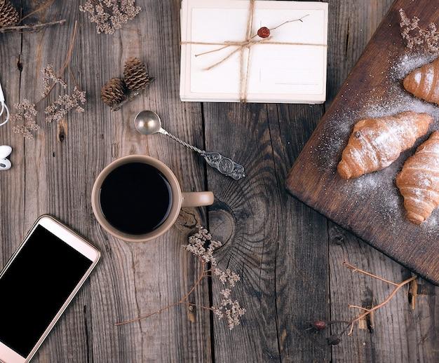 Smartphone com tela preta em branco, copo cerâmico marrom com café e croissants cozidos polvilhados com açúcar de confeiteiro Foto Premium