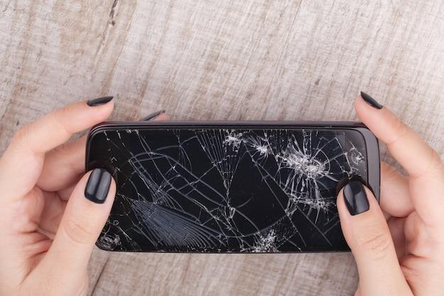 Smartphone com uma tela quebrada na mão da menina Foto Premium